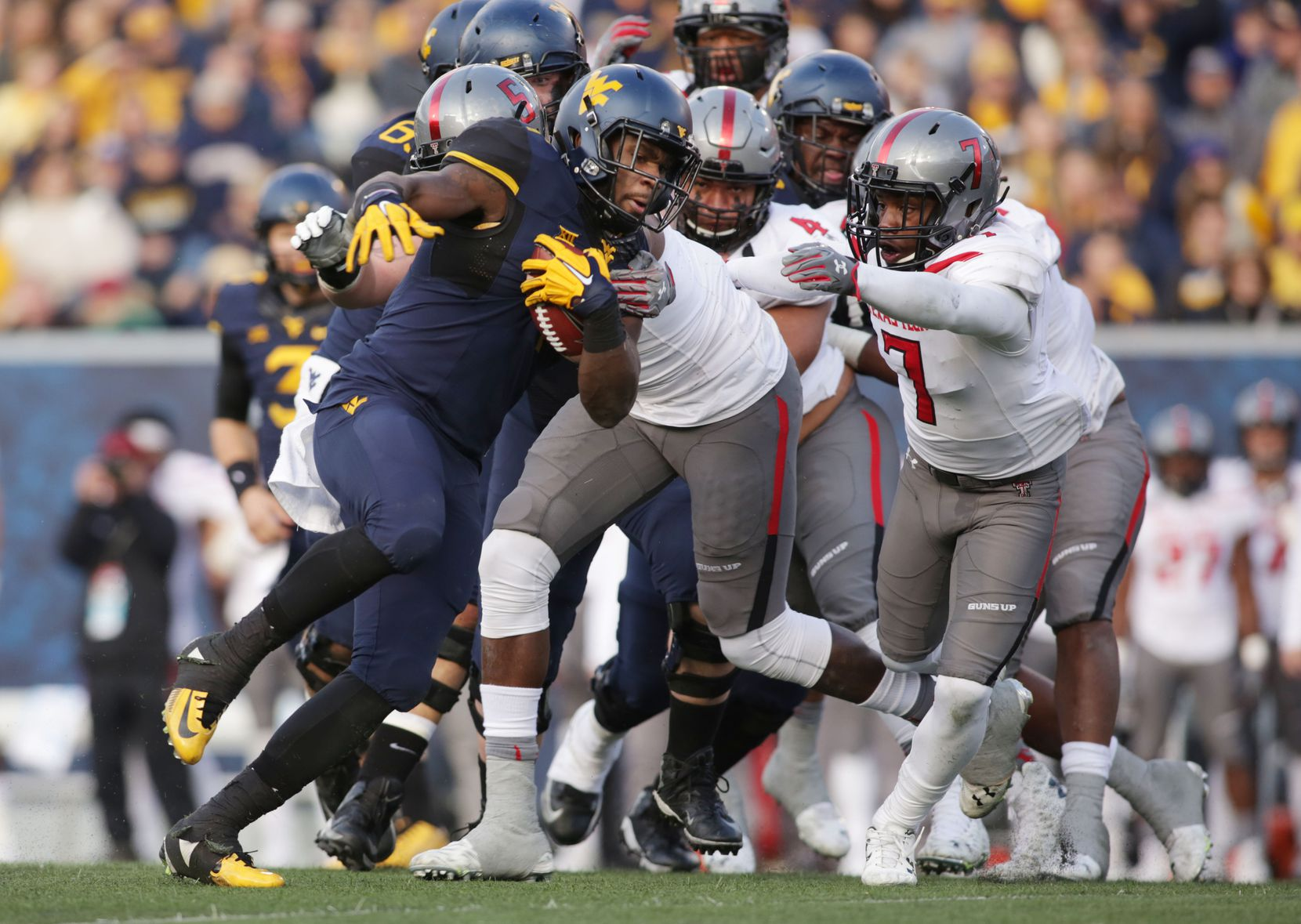 West Virginia running back Wendell Smallwood (4) is tackled by Texas Tech defensive lineman Gary Moore (5) during the second half of an NCAA college football game, Saturday, Nov. 7, 2015, in Morgantown, W.Va. West Virginia won 31-26. (AP Photo/Raymond Thompson)