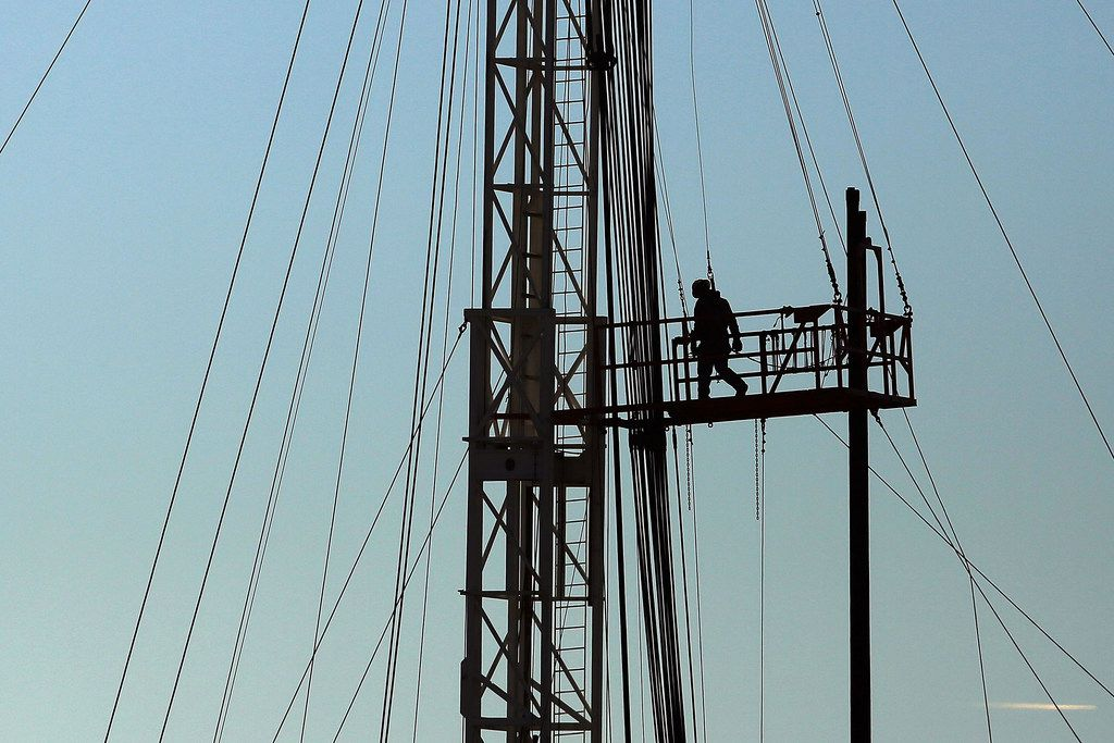 A worker for an oilfield service company works at a drilling site in the Permian Basin.