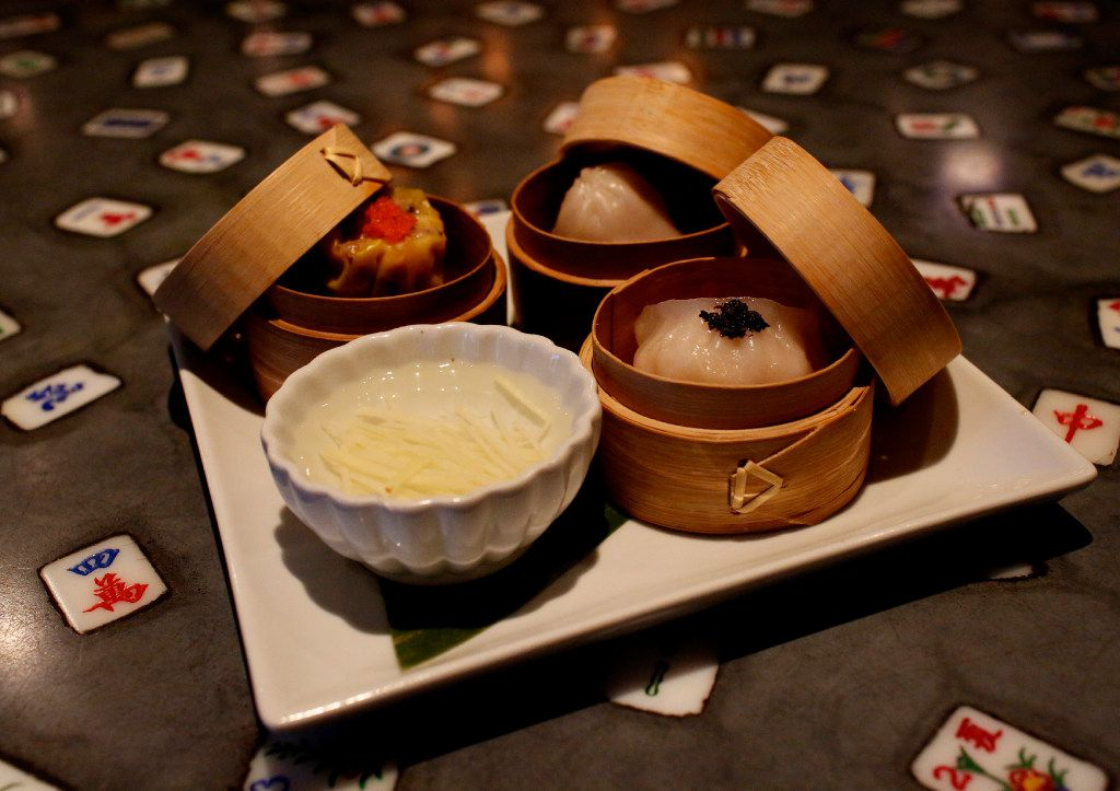 The steamed dim sum trio, an appetizer at Mah-Jong Chinese Cuisine, with shu mai (upper left), xio long bao (center), har gow with black truffle (right) and ginger-vinegar sauce. The Plano restaurant has a mah-jongg tile motif.