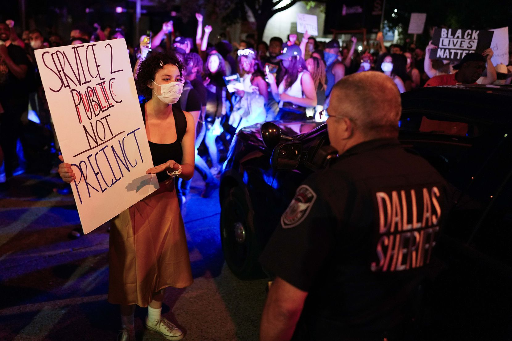 A woman confronts a Dallas County SheriffÕs deputy during a protest against police brutality as they march along Akard Street on Friday, May 29, 2020, in Dallas.