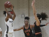 Arlington Martin's Mariah Roberts (5) passes over the defense of South Grand Prairie's Kiara Jackson (3) during second half action. The two teams played their District 8-6A  girls varsity basketball game at Arlington Martin High School in Arlington on January 26, 2021.