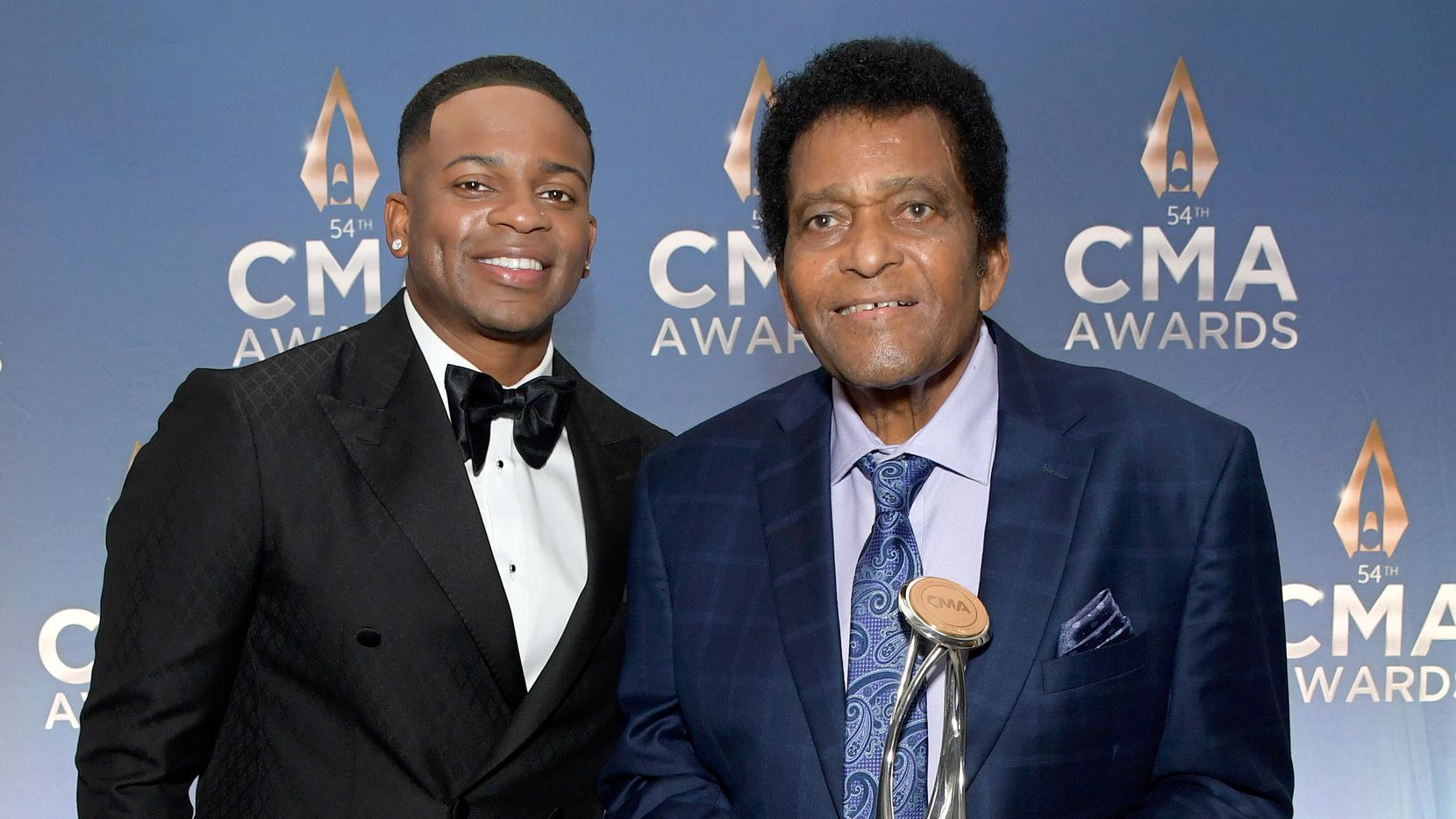 "Charley Pride (right) holds his lifetime achievement award alongside country singer Jimmie Allen at the 54th annual CMA Awards at the Music City Center on Nov. 11, 2020 in Nashville, Tenn. In a perfomance onstage during the awards, Pride, the recipient of this year's Willie Nelson lifetime achievement award at the CMAs, joined Allen onstage, where the pair sang ""Kiss An Angel Good Mornin'"" as other star entertainers sang along in the audience."