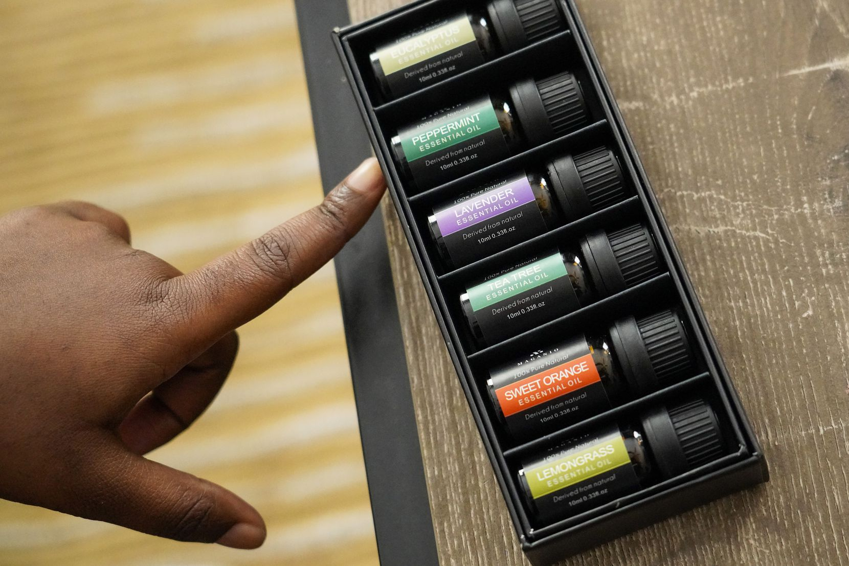Tiffani Hutton points out different essential oils she uses at her home on Wednesday, April 14, 2021, in Dallas. Hutton is part of a growing number of post-COVID patients suffering from a poorly understood condition called parosmia, a distorted sense of smell.