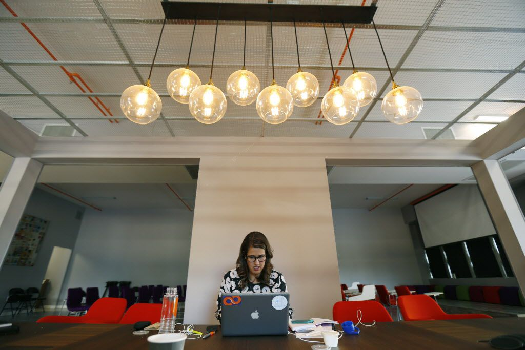 Tech Wildcatters Melanie Smith works at their new headquarters at the downtown tower in Dallas Sept. 25, 2014. (Staff Photographer/ Nathan Hunsinger)