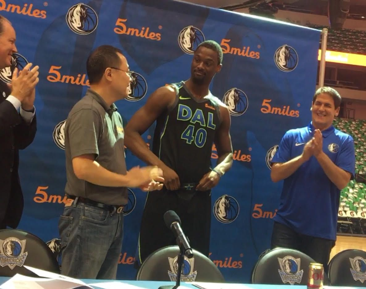 Mavericks forward Harrison Barnes models the team's jerseys featuring the new 5miles logo patch. Looking on, from left to right, are Mavericks executive VP of sponsorships George Killebrew, 5miles founder and CEO Dr. Lucas Lu and Mavericks owner Mark Cuban.
