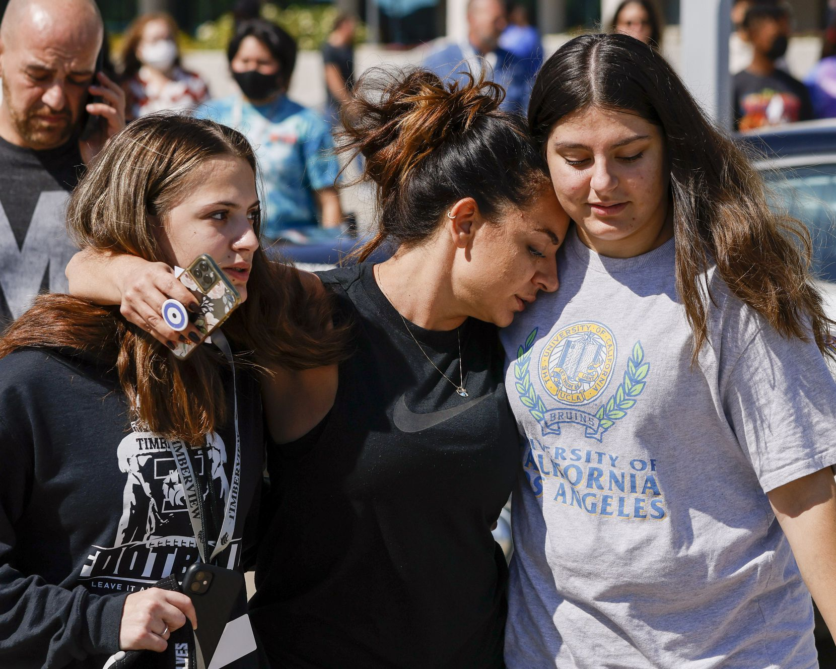 Liz Hasani (center) hugged her daughters Alivia (left) and Aminah outside the Mansfield ISD Center for the Performing Arts on Wednesday.