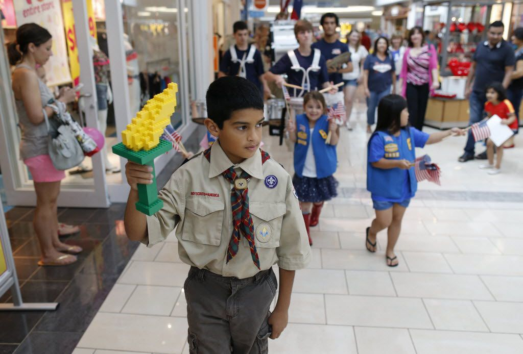 Ryan Alonzo, 10, of Carrollton holds a torch made of LEGO pieces marches in a parade with fellow boy scouts and girl scouts for a Memorial Day salute at Stonebriar Centre Mall in Frisco, on Saturday, May 23, 2015.