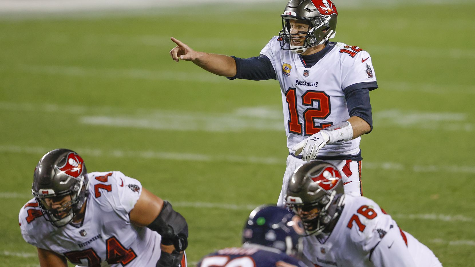 Tampa Bay Buccaneers quarterback Tom Brady (12) directs his teammates against the Chicago Bears during the second half of an NFL football game, Thursday, Oct. 8, 2020, in Chicago. (AP Photo/Kamil Krzaczynski)