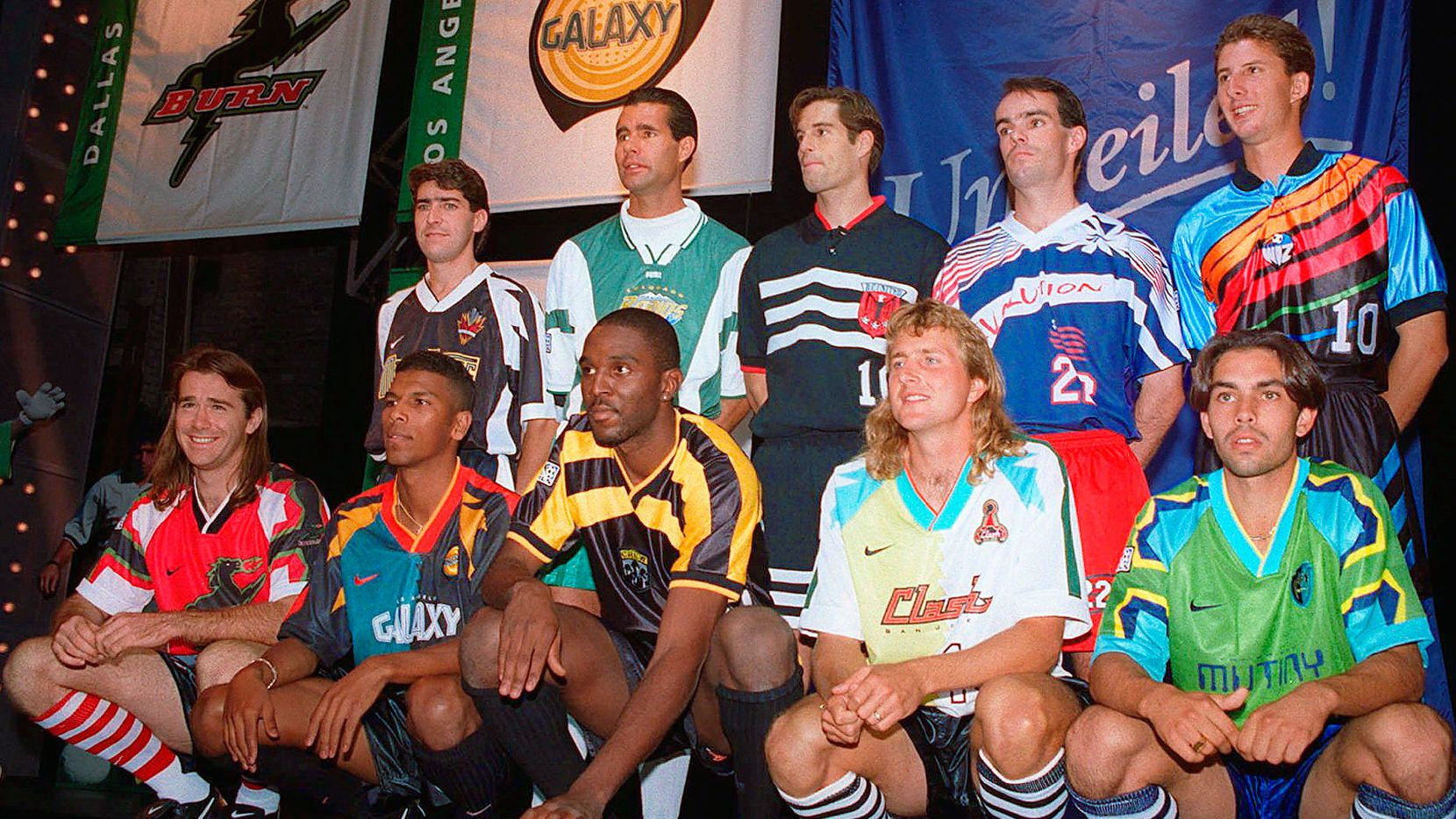 """The original 1996 MLS jersey debut.  Back row, left to right: Tab Ramos (NY/NJ MetroStars), Roy Wegerle (Colorado Rapids), John Harkes (DC United), MIke Burns (New England Revolution), and MIke Sorber (Kansas City Wiz).  The front row are """"models"""" hired for the event to represent: Dallas Burn, LA Galaxy, Columbus Crew, San Jose Clash, Tampa Bay Mutiny."""