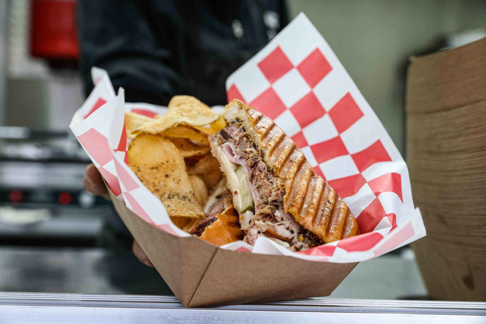 Chef Jordan Savell presents El Cubano, her signature cuban sandwich with smoked pork shoulder, ham, swiss cheese, chef J's pickles, horseradish mustard and cuban bread in her food truck Bullfish Foods in Fort Worth on Wednesday, March 24, 2021.