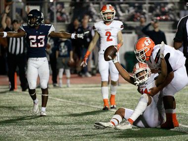 Rockwall's Jaxon Smith-Njigba (11) holds the ball high, but Allen's Mo Perkins (23) say no, after Smith-Njigba's touchdown during the first quarter of the Class 6A Division I Region II area-round football playoff game at Williams Stadium in Garland on Friday, November 23, 2018. (John F. Rhodes / Special Contributor)