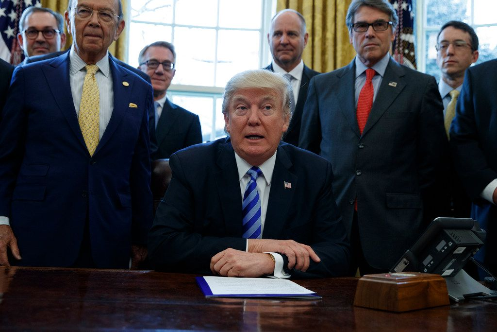 This March 24, 2017, file photo shows President Donald Trump, flanked by Commerce Secretary Wilbur Ross, left, and Energy Secretary Rick Perry.