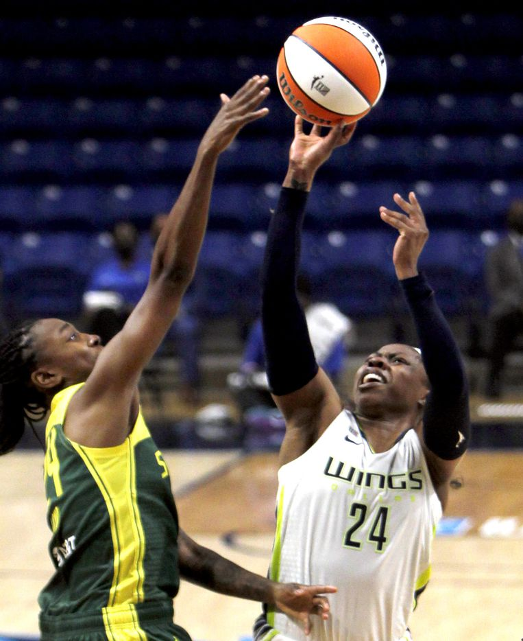 Dallas Wings guard Arike Ogunbowale (24) puts up a shot against the tight defense of Seattle guard Jewell Loyd (24) during first half action. The Wings hosted the Storm for their WNBA 2021season home opener at UTA's College Park Center in Arlington on May 22, 2021. (Steve Hamm/ Special Contributor)