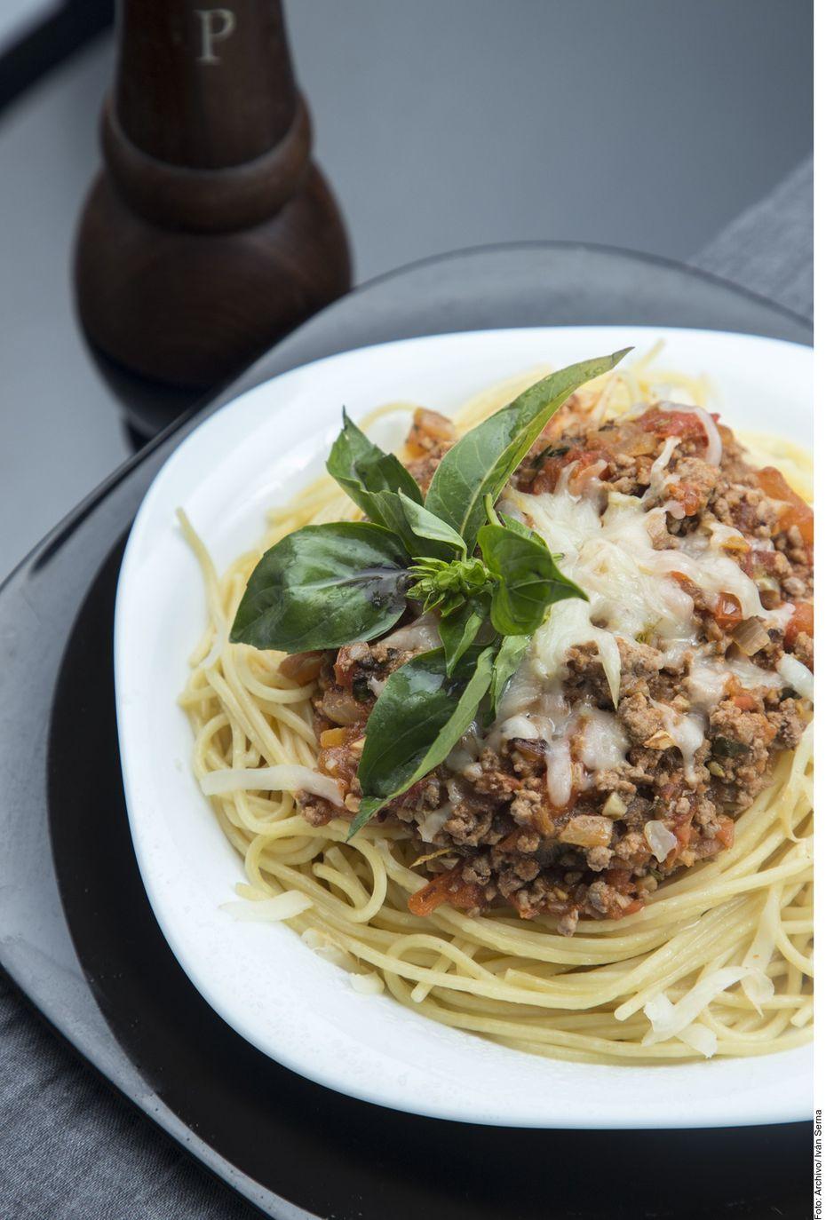 El espagueti a la boloñesa se logra al calentar el aceite a fuego medio y freír el ajo. Añadir la cebolla y acitronar. Subir el fuego e incorporar la carne, cocinar durante 10 minutos. Agregar el jitomate, el puré y las hierbas de olor.