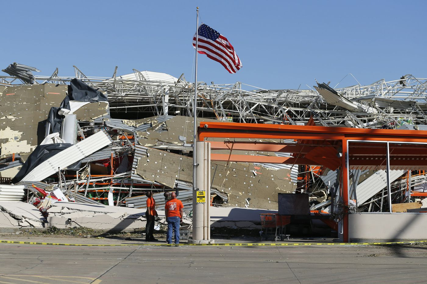 The Home Depot employees A.J. Kobena (center) raises the U.S. flag on the flagpole outside the destroyed store on N. Central Expressway in Dallas, Monday, October 21, 2019. Joining him were fellow employees Jonathan Shields and Jordan Jasper (left). A tornado tore through the entire neighborhood knocking down trees and ripping roofs from homes. (Tom Fox/The Dallas Morning News)