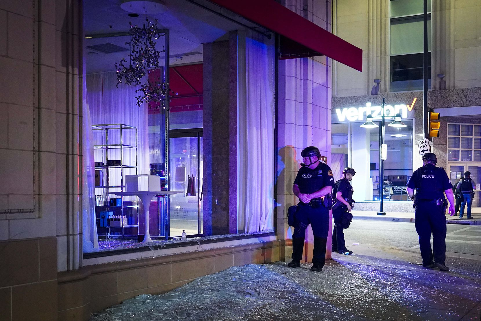 Dallas police stand guard amidst broken glass after windows were smashed at the Nieman Marcus store downtown following a protest against police brutality in the early morning hours of Saturday, May 30, 2020, in Dallas.
