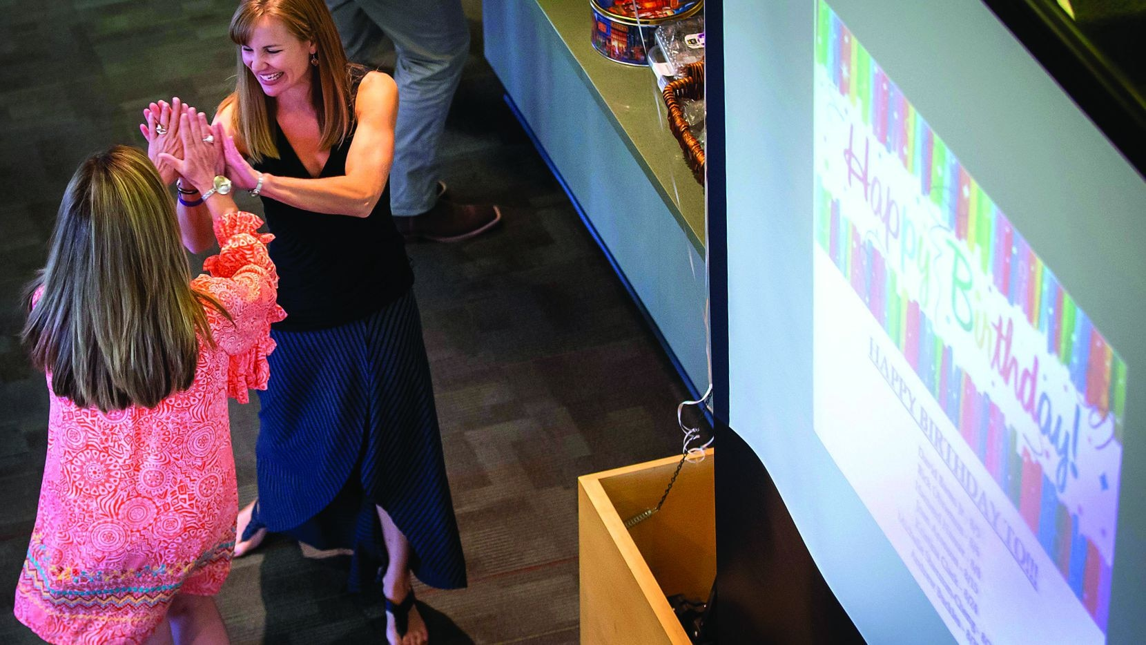 Lindsay Hendricks (facing) high fived a co-worker during a party celebrating employee birthdays at Systemware in 2018.