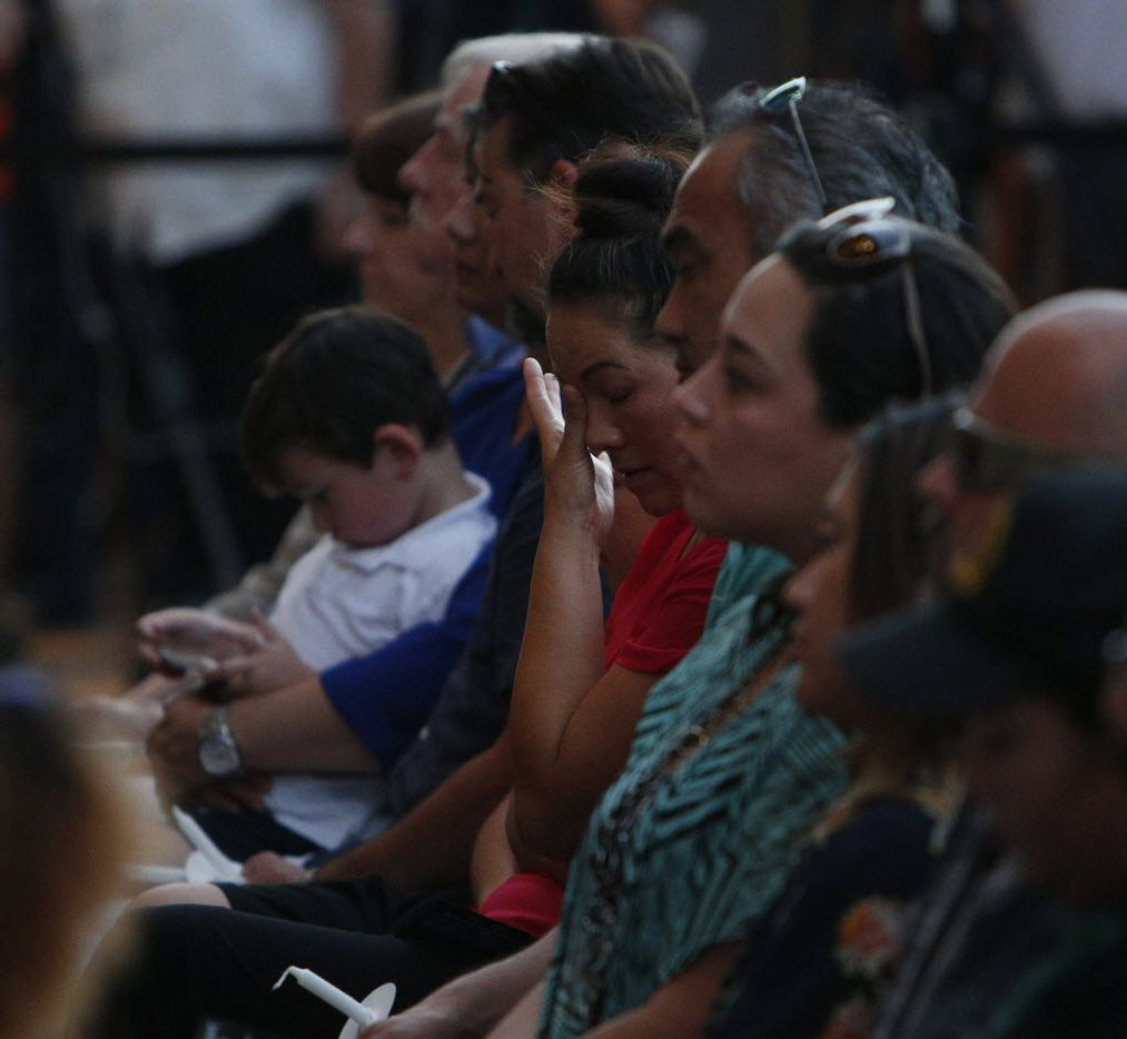 A family member wipes away a tear during a candlelight vigil hosted by the Dallas Police Association at Dallas City hall in Dallas, TX July 11, 2016. (Nathan Hunsinger/The Dallas Morning News)