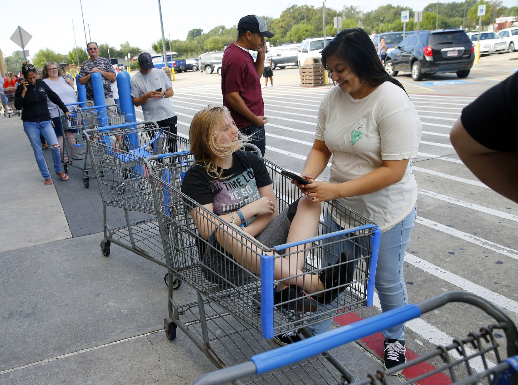 Jessica Puffen, 16, waited in a shopping cart along with her friend Emily Gomez, 17,  in a long line at  the Walmart on Hwy. 35 in Pearland, Texas.