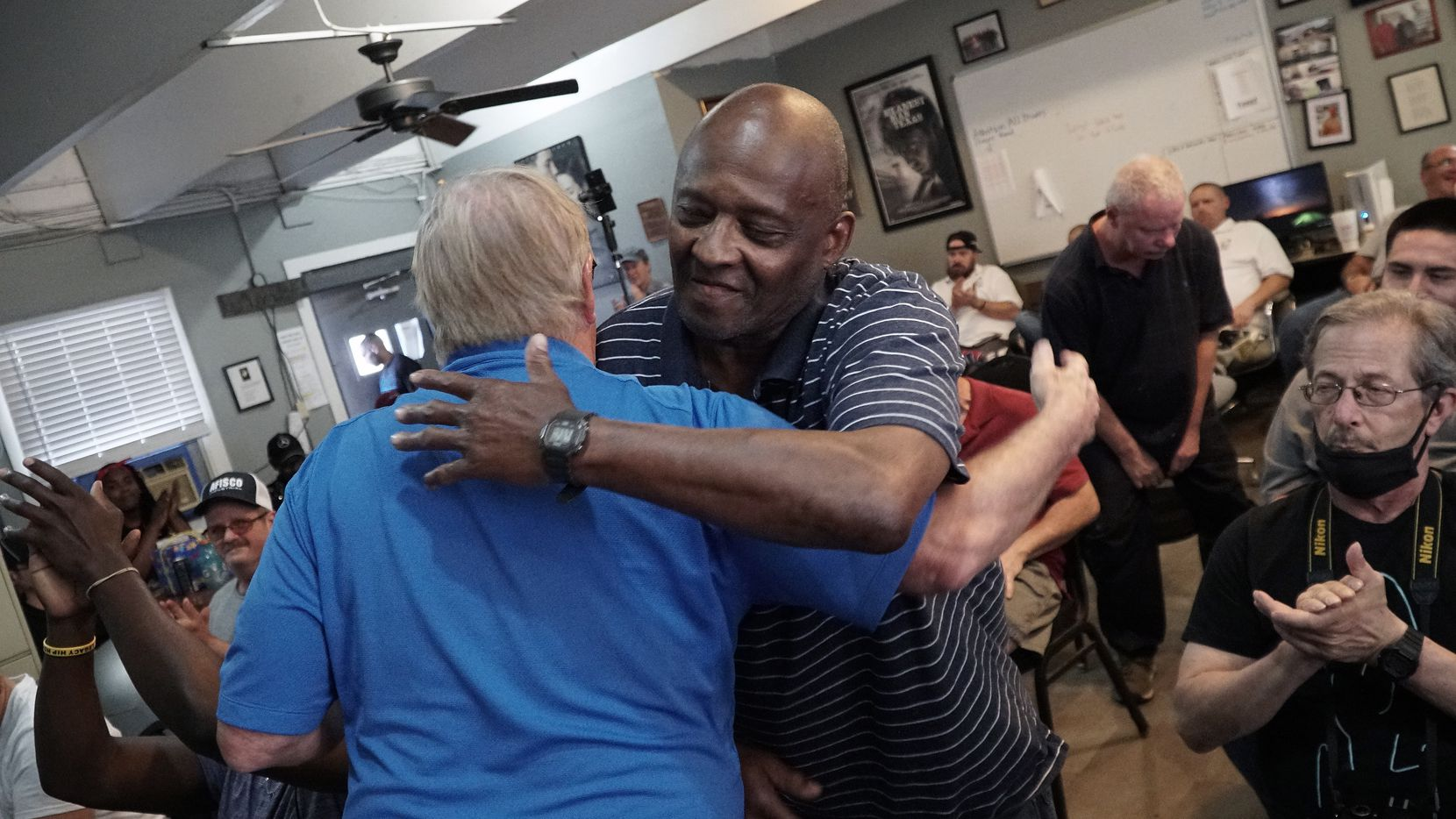 Tony Jackson (right) hugs Brent Burmaster after receiving a sobriety chip during a meeting at Soul's Harbor in Dallas. Burmaster is the shelter's executive director.