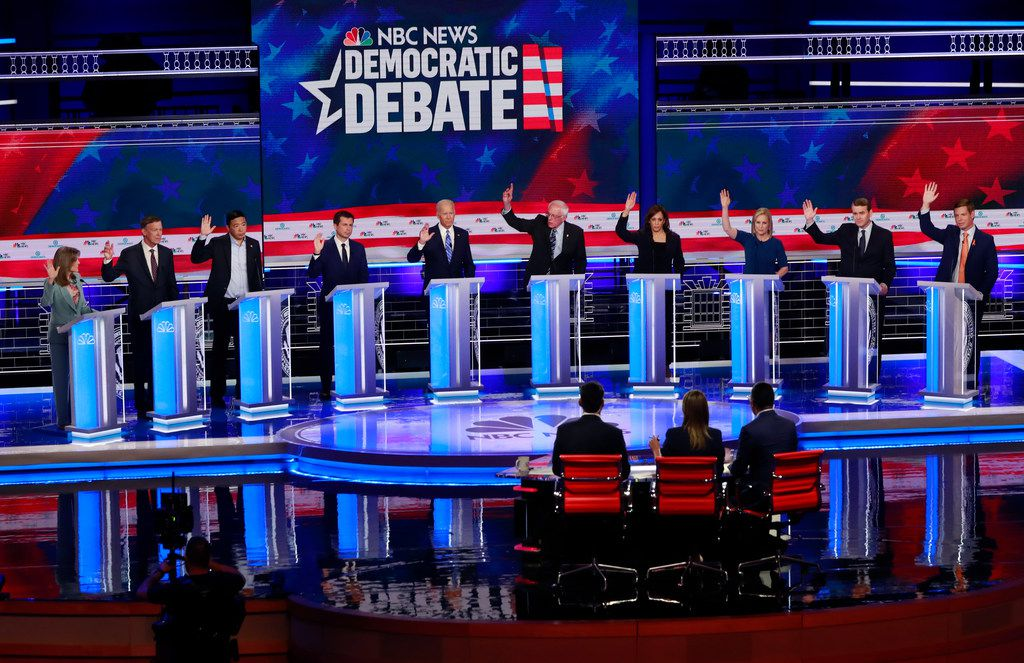 Democratic presidential candidates (from left), author Marianne Williamson, former Colorado Gov. John Hickenlooper, entrepreneur Andrew Yang, South Bend Mayor Pete Buttigieg, former Vice President Joe Biden, Sen. Bernie Sanders, I-Vt., Sen. Kamala Harris, D-Calif., Sen. Kirsten Gillibrand, D-N.Y., Colorado Sen. Michael Bennet, and Rep. Eric Swalwell, D-Calif., raise their hands when asked if they would provide health care for unauthorized immigrants during the recent Democratic primary debate hosted by NBC News at the Adrienne Arsht Center for the Performing Arts in Miami.