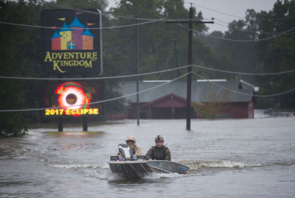Emergency responders drive a boat across Highway 96 in floodwaters in Lumberton.