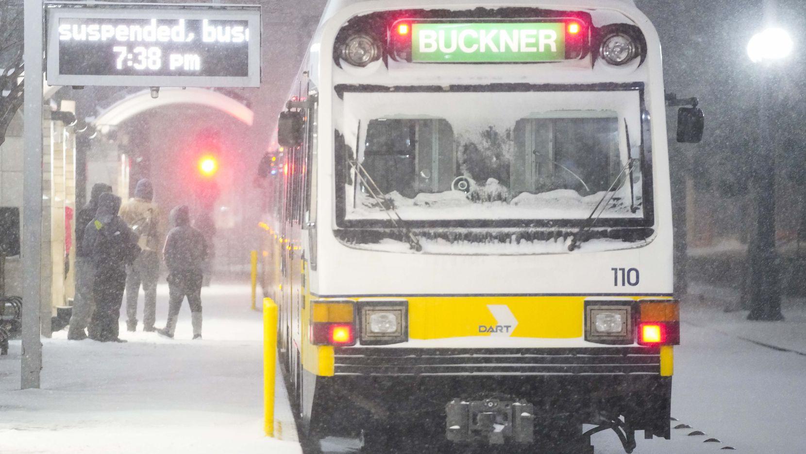 Usuarios esperan bajo la nieve para abordar uno de los autobuses de DART en el área Pearl/Arts District, el 14 de febrero de 2021 en Dallas.