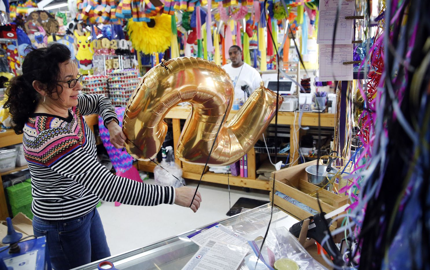 """On one of the last days before the shelter-in-place order closed nonessential businesses in Dallas County, Elvie De La Fuente inflated balloons for a birthday party for the daughter of customer Alexander Mitchell (background). """"Were going to get through it."""" she said fighting back tears."""