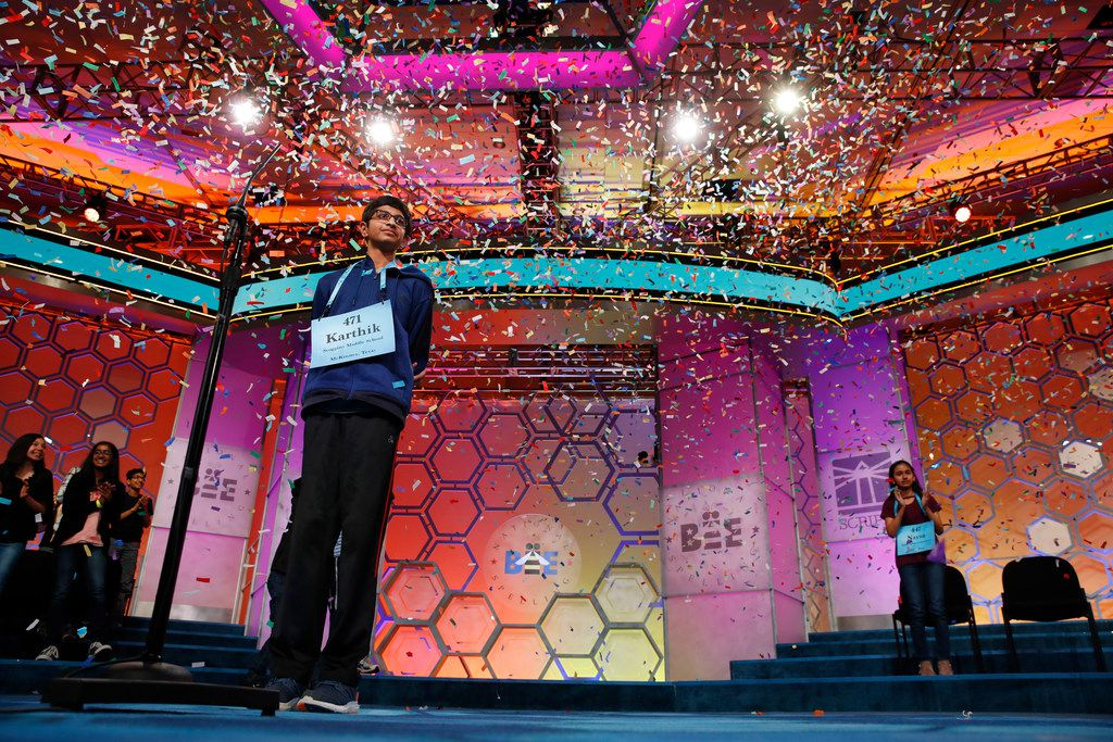 Karthik Nemmani, 14, from McKinney, Texas, left, watches as confetti falls as he wins the Scripps National Spelling Bee in Oxon Hill, Md., Thursday, May 31, 2018. At right is runner up Naysa Modi, 12, from Frisco, Texas. (AP Photo/Jacquelyn Martin)