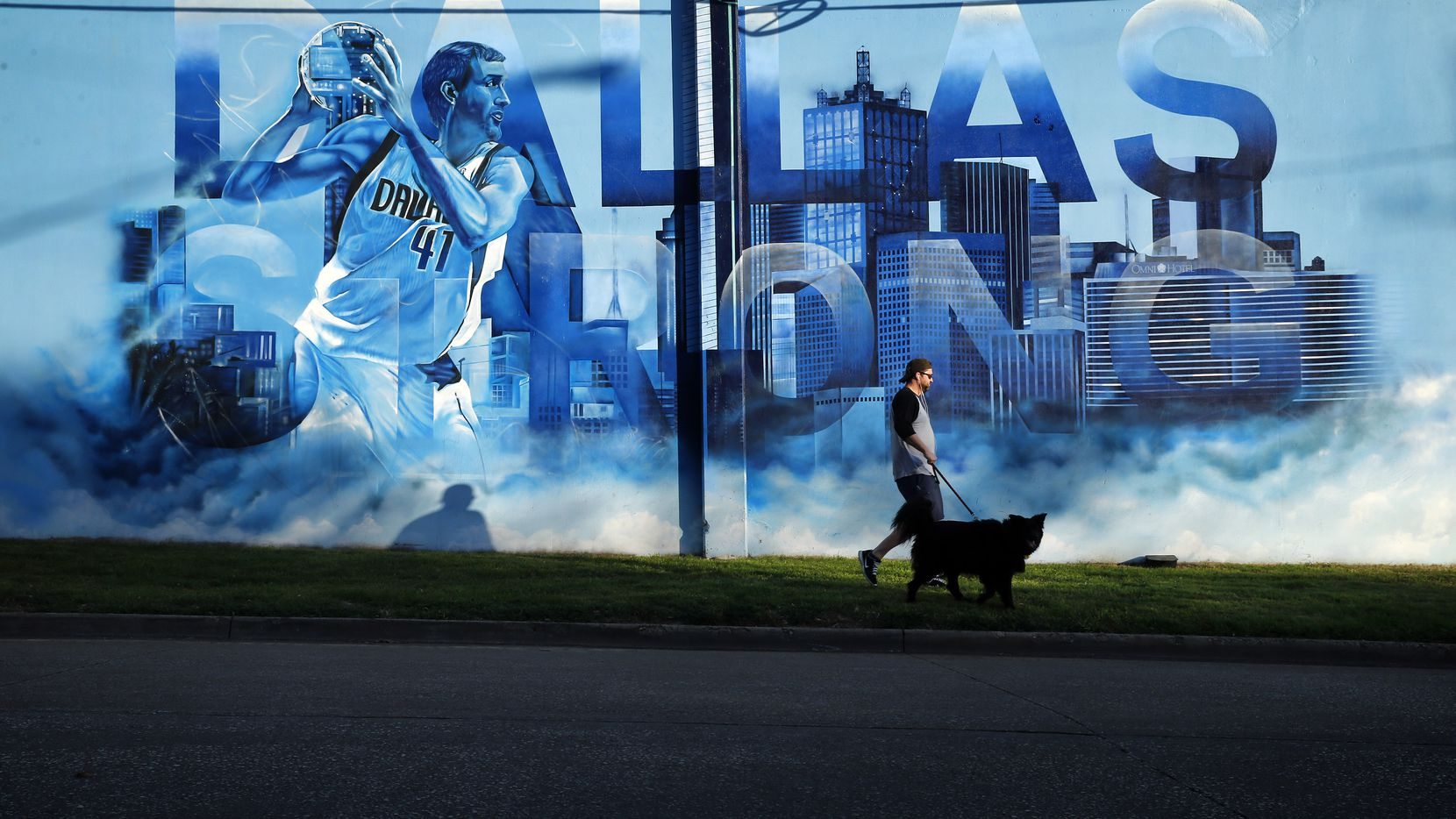 Scott Mitchell of Dallas walks his border collie Arthur past an image of Dallas Mavericks forward Dirk Nowitzki, which is displayed on the side of the team's practice facility near downtown Dallas.