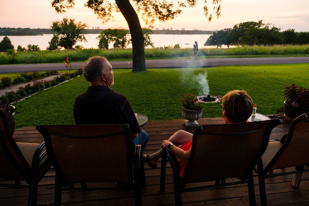 Shirley Zsohar (right) and her neighbor Joe Gillum watch the sunset from the front yard of Zsohar's home overlooking White Rock Lake on Thursday, Aug. 8, 2019, in Dallas. (Smiley N. Pool/The Dallas Morning News)