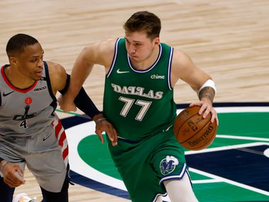 Dallas Mavericks guard Luka Doncic (77) handles the ball as Washington Wizards guard Russell Westbrook (4) tries to slow him down during the first half of an NBA basketball game Saturday, May 1, 2021, in Dallas. (AP Photo/Ron Jenkins)