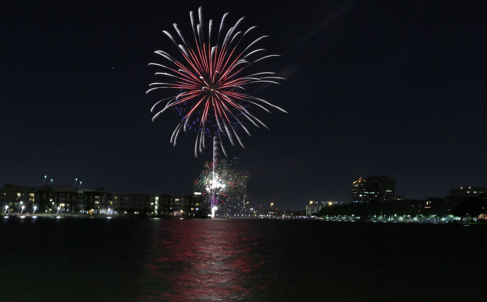 Fireworks light up the sky over Irving in 2018, with the dazzling effects reflected in Lake Carolyn. This year's July 4 festivities, at Levy Event Plaza, include music by Alex Aguilar and Downtown Fever followed by fireworks.