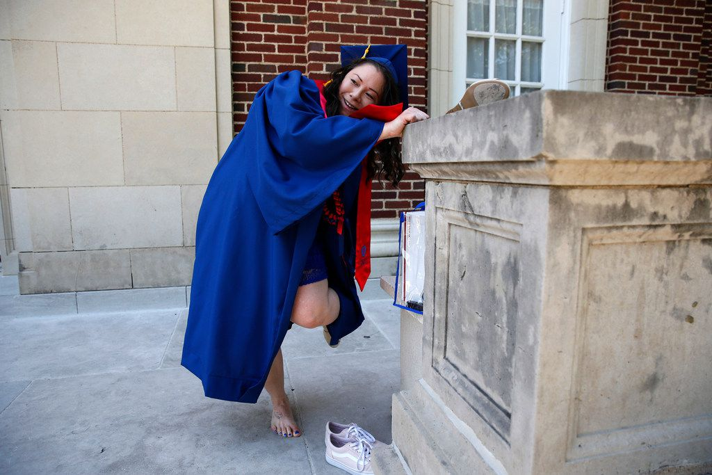 Wendy Birdsall switches shoes before graduation from SMU at McFarlin Auditorium on Friday.