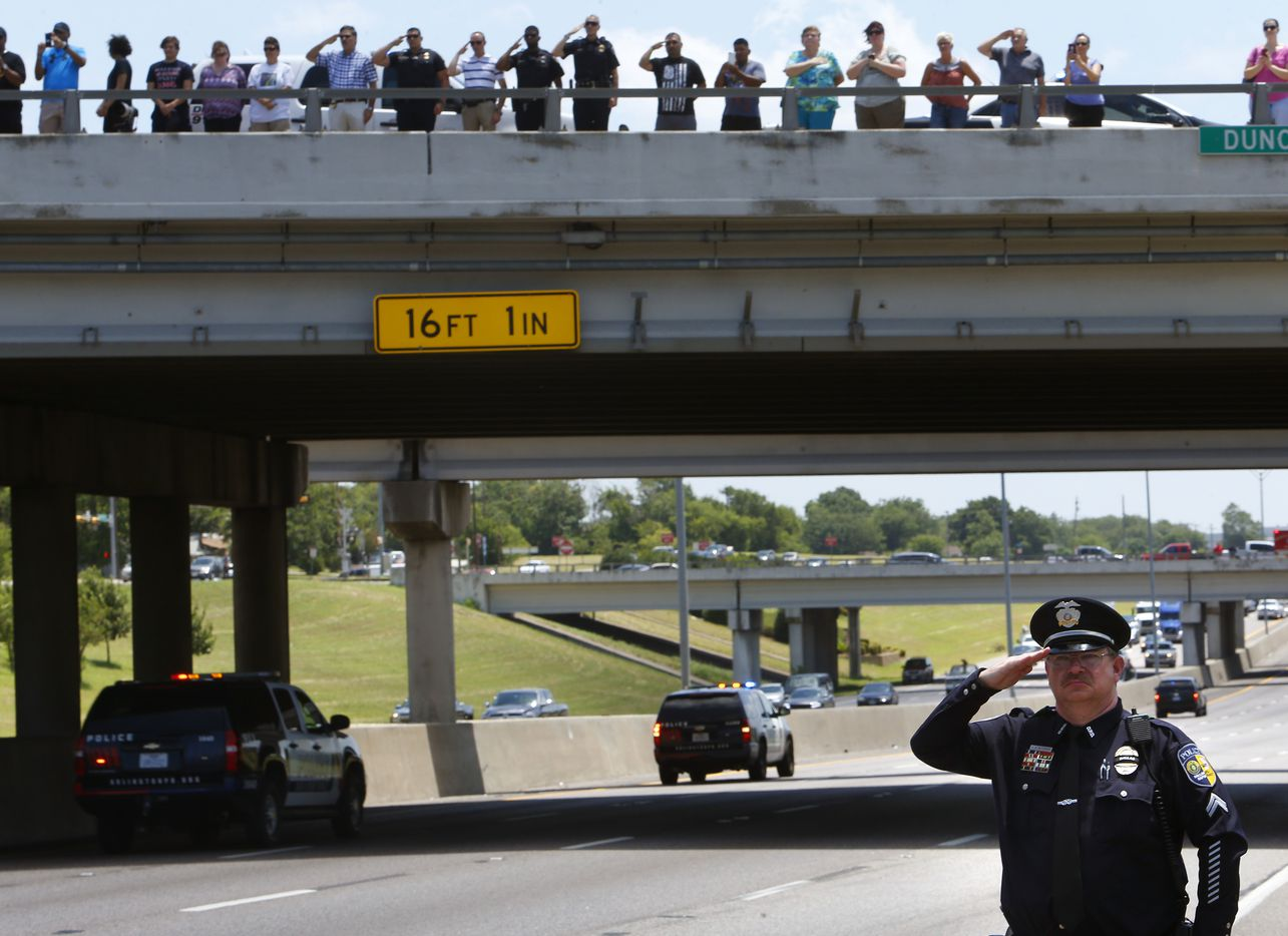 DART Corporal Gary Hutchison salutes the funeral procession for DART Officer Brent Thompson on Interstate 20 in Duncanville, Texas on Wednesday, July 13, 2016. Thompson and four other officers were killed during an attack during a peaceful Black Lives Matter protest on July 7, 2016.