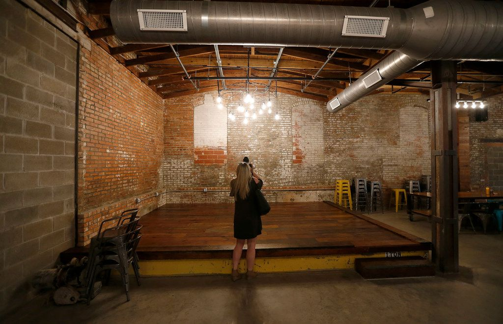 Guest Sarah Karger takes pictures of the lighting of the stage inside the taproom at the new Four Corners Brewing Co. facility in the Cedars neighborhood in Dallas, Wednesday, Oct. 18, 2017.