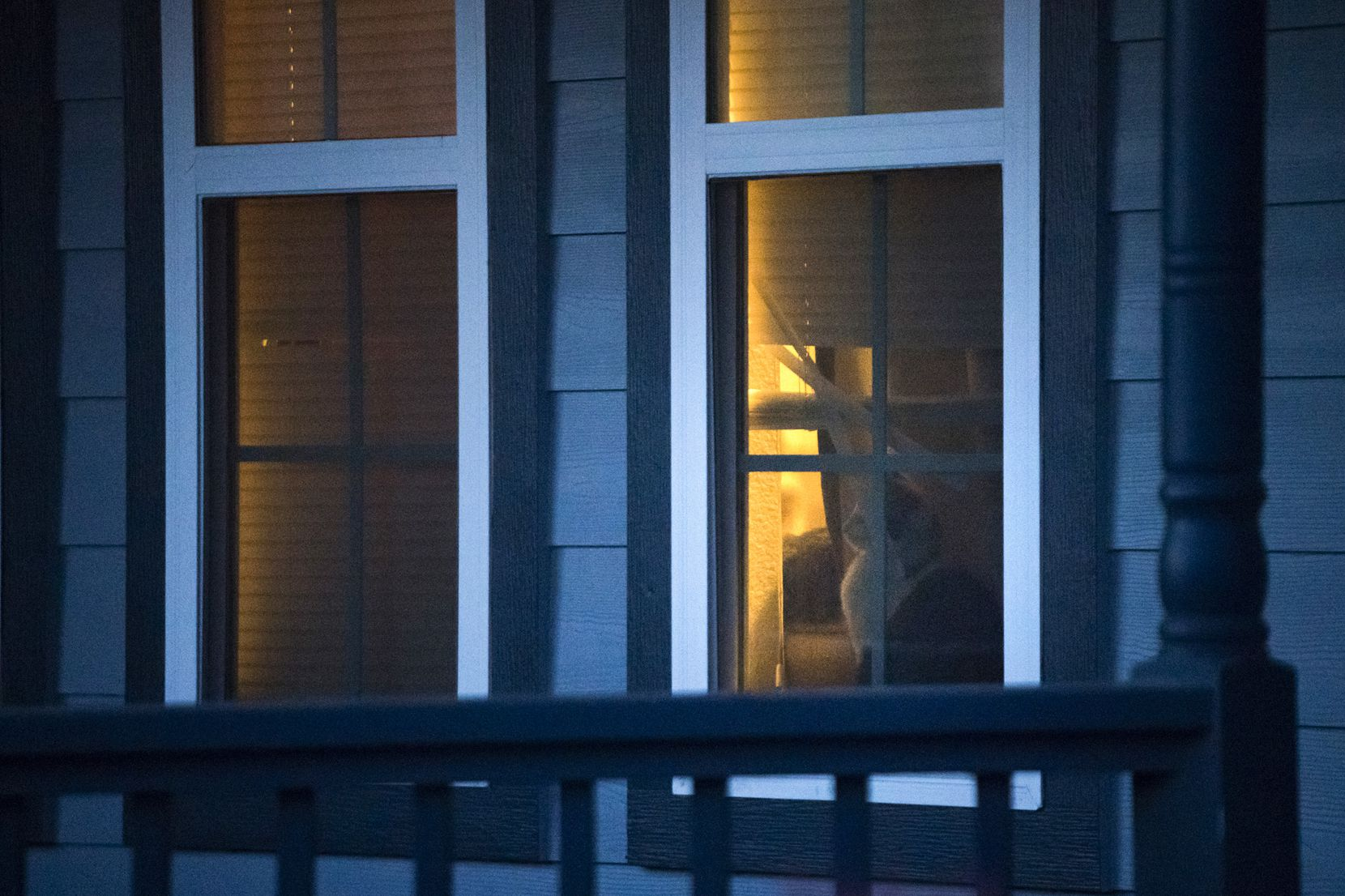 A cat is seen through the window of the house where Atatiana Jefferson was shot and killed during a community vigil for Jefferson on Sunday, Oct. 13, 2019, in Fort Worth.