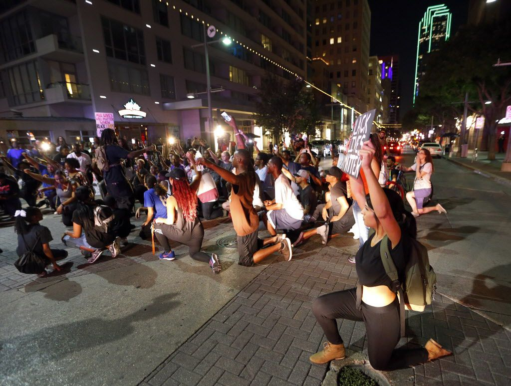 Like San Francisco quarterback Colin Kaepernick, protesters take a knee in the intersection of Main St. and S. St. Paul forcing the police to move in with riot gear during the Next Generation Action Network protest in downtown Dallas, Thursday, September 22, 2016. In response to the police killings, the group is standing in solidarity with the families and all of those who want justice for all. (Tom Fox/The Dallas Morning News)