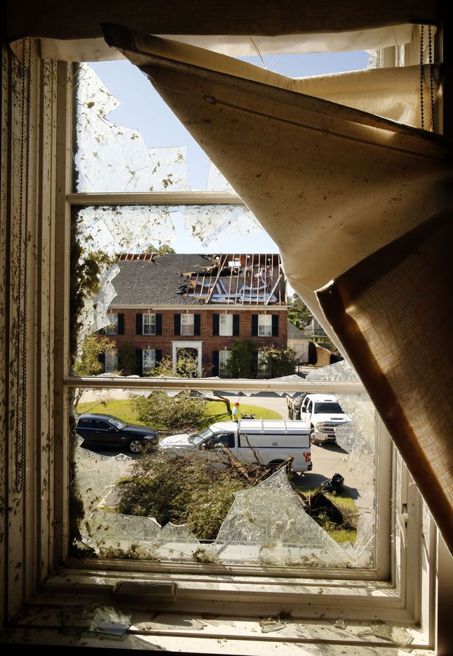 Damaged homes on Pemberton Drive are seen through Eva Wiley's window in Dallas, Monday, October 21, 2019. A tornado tore through the neighborhood knocking down trees and ripping roofs from homes.