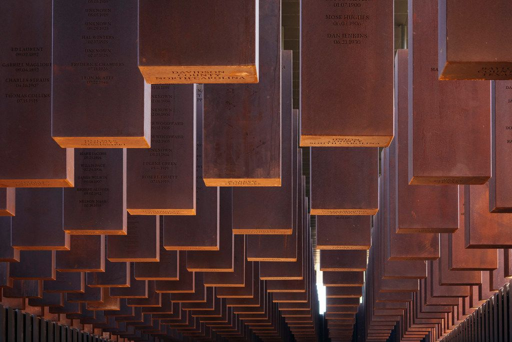 Some of the 800 weathered steel columns, each one etched with the names of a lynching victim, hang from the roof of the new National Memorial for Peace and Justice in Montgomery, Ala., April 20, 2018. The six-acre site overlooking the state capital demands a reckoning with with one of the nation's least recognized atrocities, a decades-long campaign of racist terror.