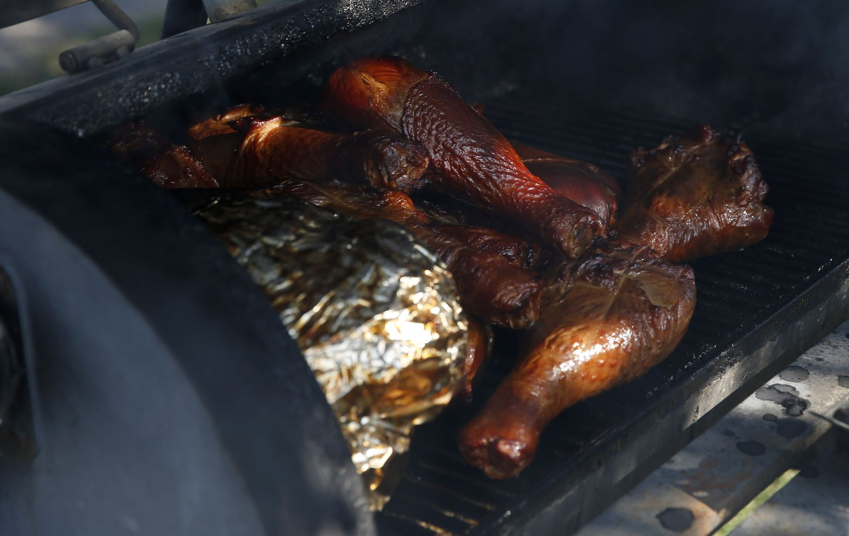 Wrapped brisket sits beside turkey legs on the barbecue pit tended by Stacey Walker on Saturday, Oct. 10, 2020. Although the grill masters of this group are diehard fans of their respective teams, the UT-OU game has turned them into unlikely friends, and over the years, family. (Vernon Bryant/The Dallas Morning News)