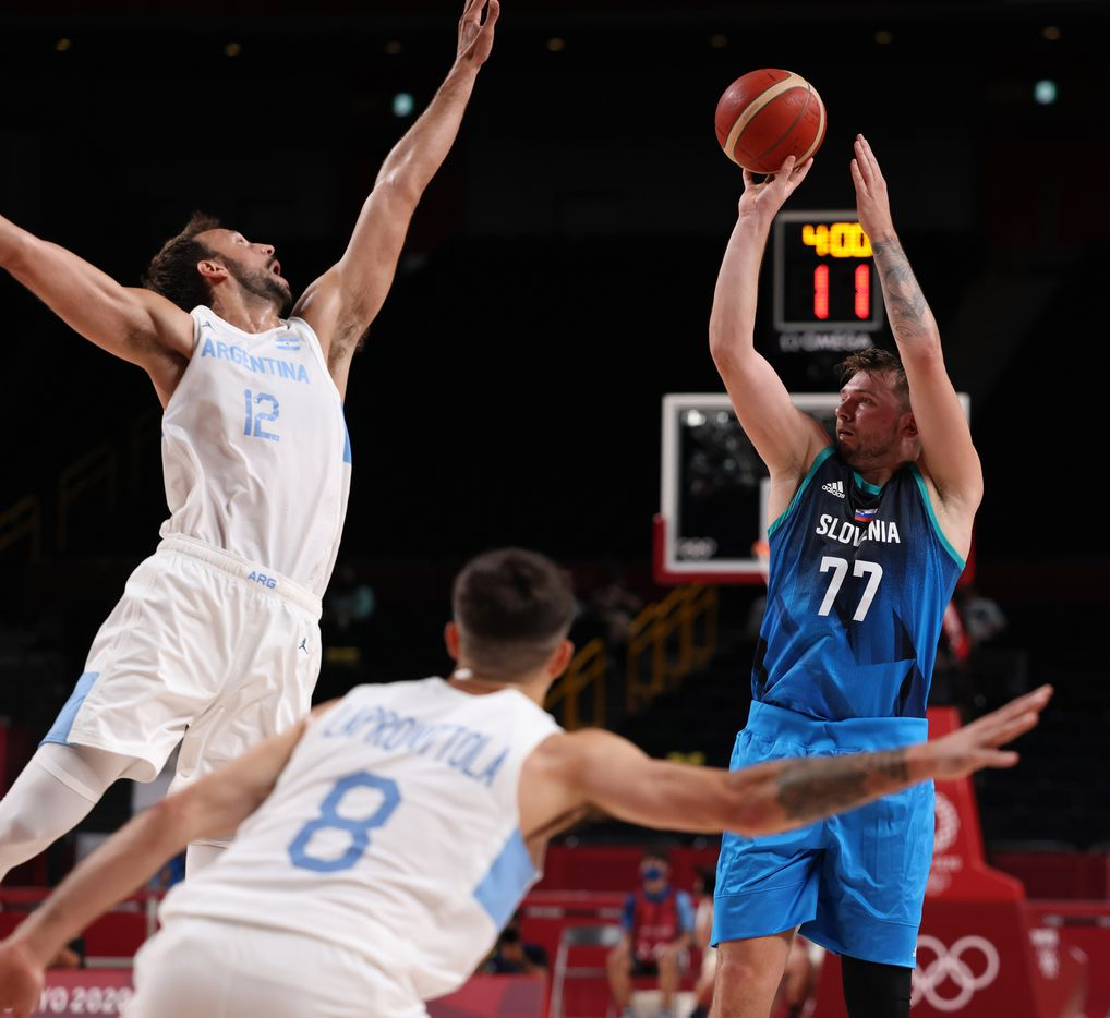 Slovenia's Luka Doncic (77) shoots over Argentina's Marcos Delia (12) as Nicolas Laprovittola (8) closes in on the play during the postponed 2020 Tokyo Olympics at Saitama Super Arena on Monday, July 26, 2021, in Saitama, Japan. Slovenia defeated Argentina 118-100. (Vernon Bryant/The Dallas Morning News)