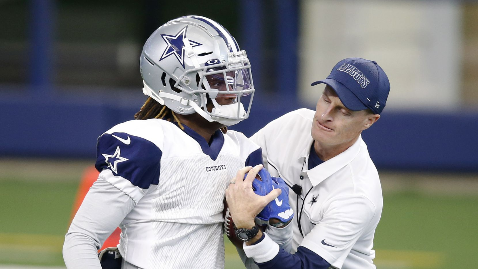 Dallas Cowboys special teams coordinator John Fassel attempts to take the ball away from Dallas Cowboys wide receiver CeeDee Lamb (88) in practice on Cowboys Night during training camp at AT&T Stadium in Arlington, Texas on Sunday, August 30, 2020.