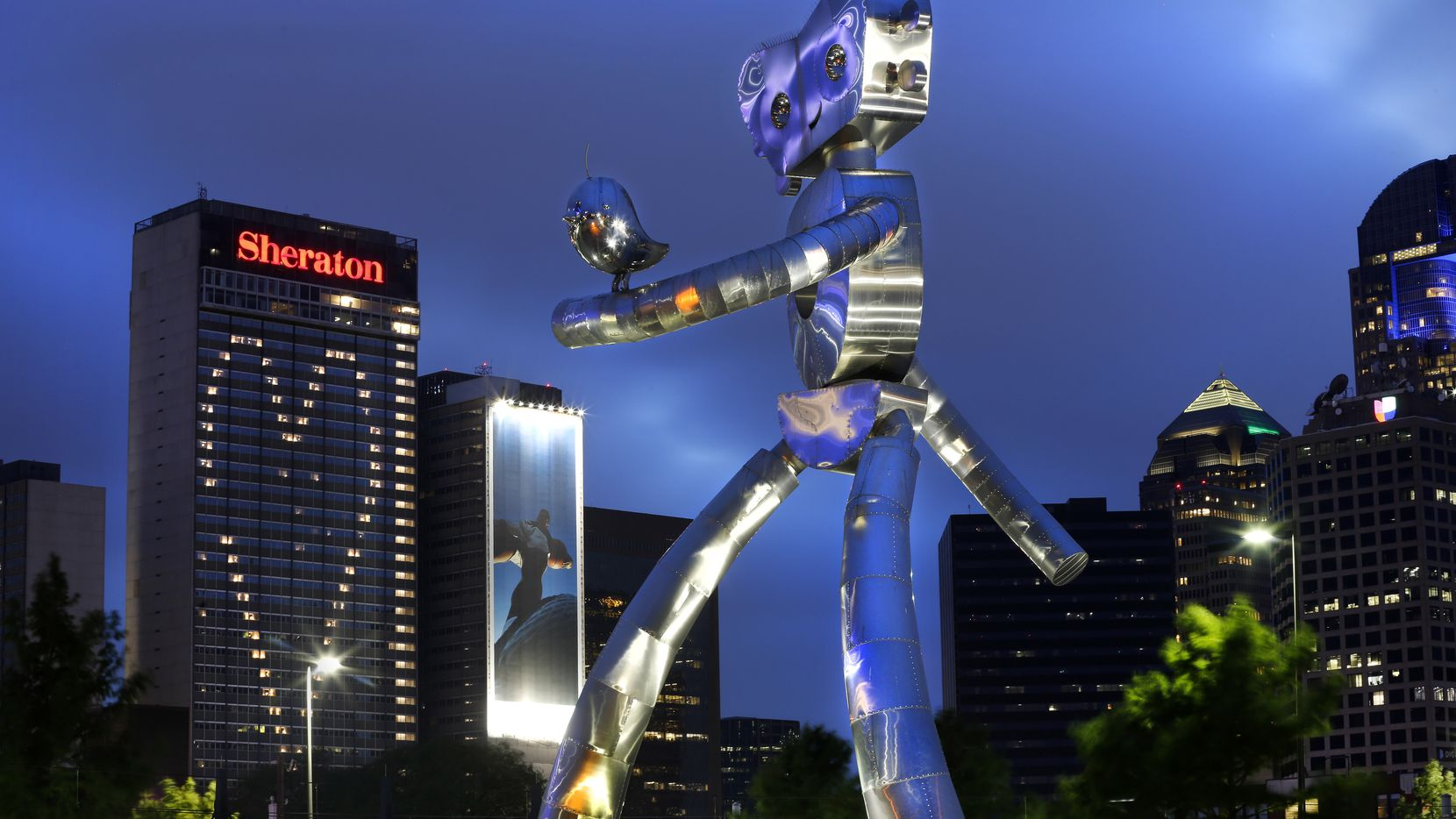 The Traveling Man reflective structural steel sculpture photographed Wednesday night in downtown Dallas. As North Texans prepare to navigate vacations, road trips and summer fun, we'll all have to pick our way carefully through the coronavirus health crisis.