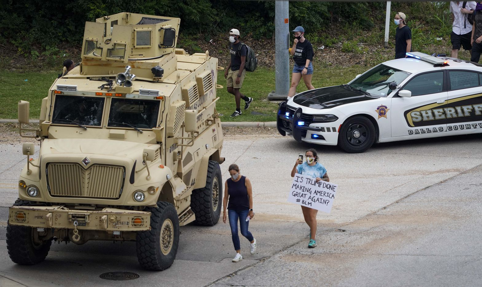 Demonstrators pass law enforcement vehicles as they head to a rally the Frank Crowley Courts Building as protests continue after the death of George Floyd on Monday, June 1, 2020, in Dallas.