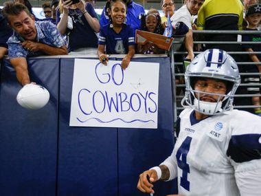 El mariscal de los Dallas Cowboys, Dak Prescott, firma autógrafos antes de una práctica en Frisco, el 26 de agosto de 2019.