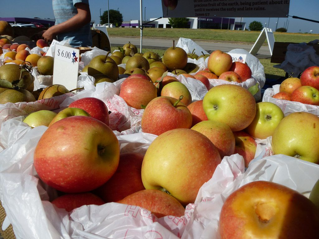 Apples like these from J&L Family Farm in Bowie are among the surprise finds that await at Cowtown Farmers Market. Behind them are Asian pears and peaches.