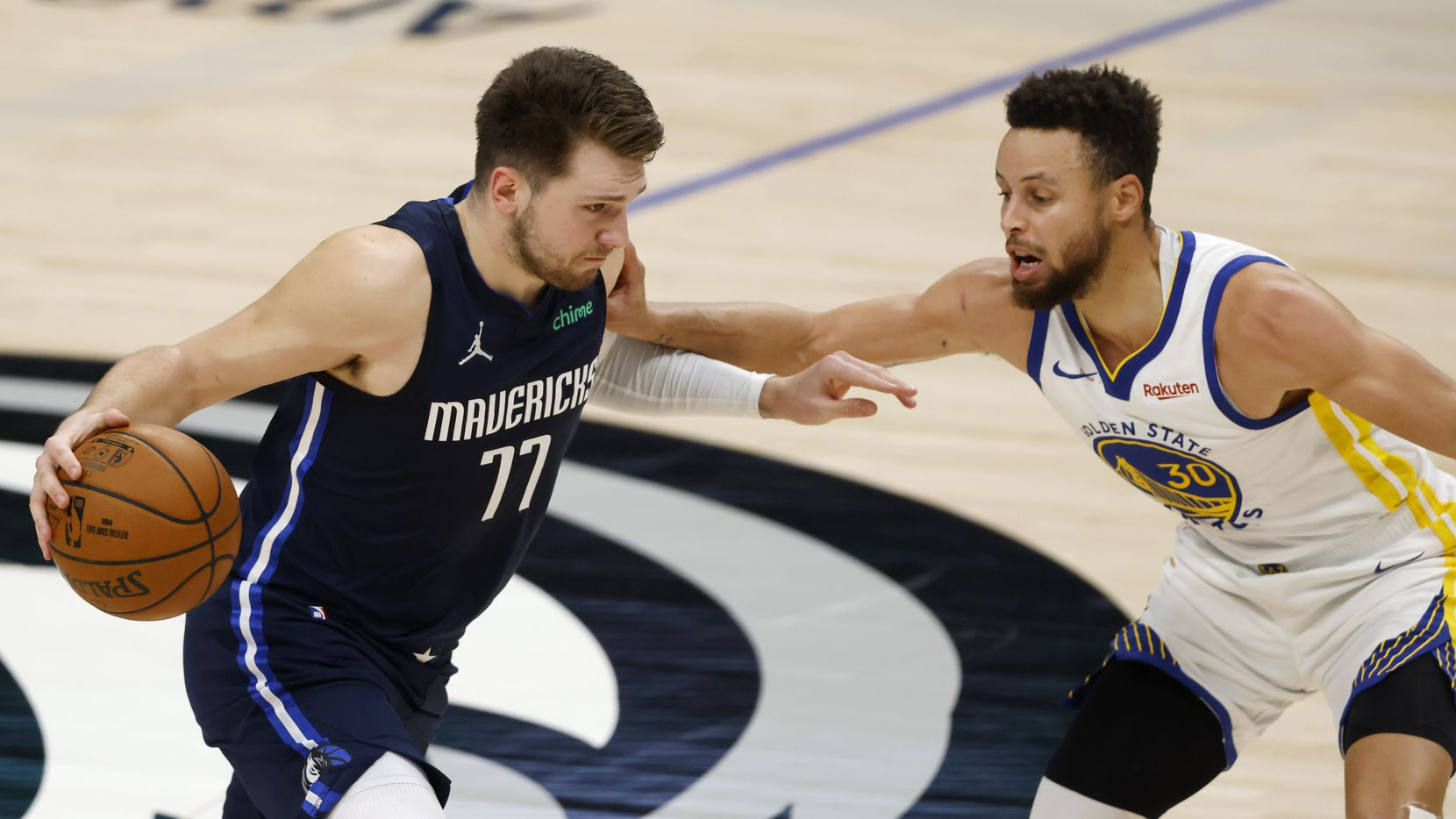 Dallas Mavericks guard Luka Doncic (77) drives on Golden State Warriors guard Stephen Curry (30) during the third quarter of play at American Airlines Center on Saturday, February 6, 2021 in Dallas.