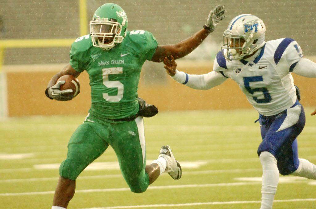 University of North Texas senior  running back Lance Dunbar (5) fends off a tackle by Middle Tennessee State University senior corner Arness Ikner (5), Saturday, December 3, 2011, at Apogee Stadium in Denton, Texas. (DAVID MINTON/STAFF PHOTOGRAPHER)