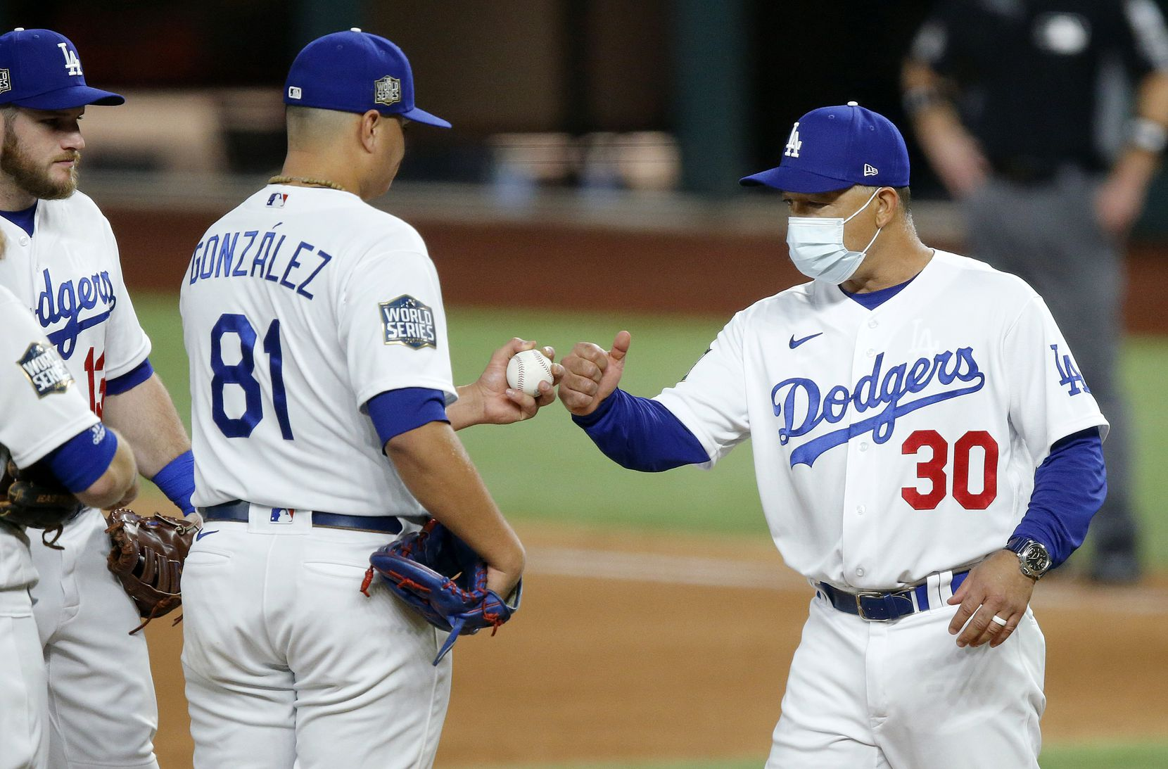 Los Angeles Dodgers manger Dave Roberts gives relief pitcher Victor Gonzalez (81) a fist bump as he pulls him during the fourth inning against the Tampa Bay Rays in Game 2 of the World Series at Globe Life Field in Arlington, Wednesday, October 21, 2020. (Tom Fox/The Dallas Morning News)